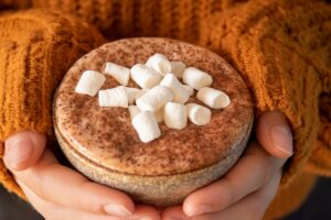 thermomix hot chocolate in mug with marshmallows being held with two hands, person wearing snuggly orange jumper