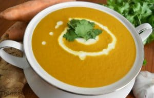 sweet potato soup thermomix made, in white bowl with two handles. Blurred vegetables in background