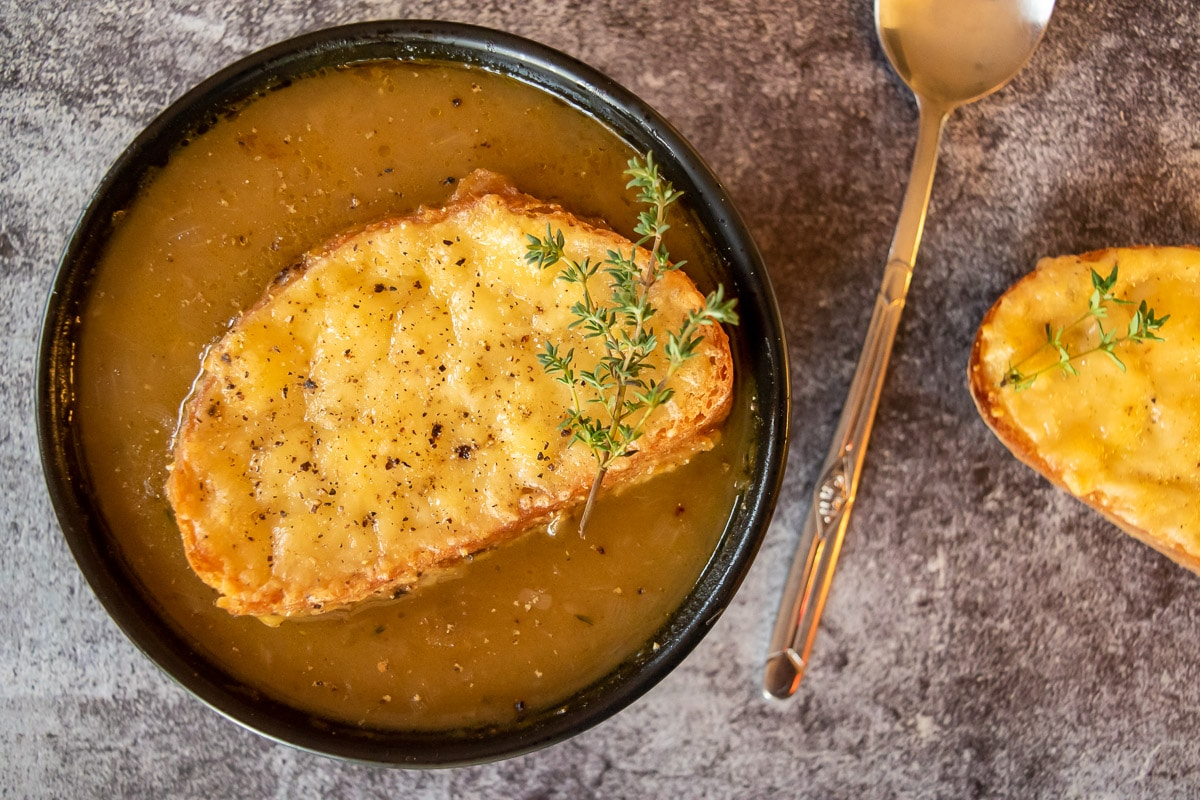 french onion soup in black bowl, with cheesie on top, spoon on right with cheesie right of the spoon