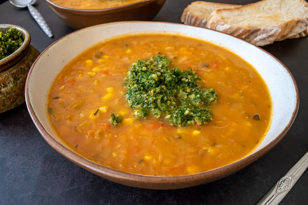 very veggie soup thermomix in bowl with pesto on top, pesto in bowl and toast and another bowl of soup in background. All on black surface.