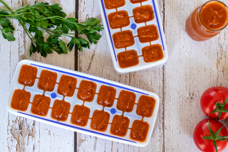 Thermomix tomato paste in ice cube trays and jar on white wood with parsley and tomatoes on vine