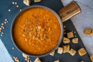 spicy tomato and lentil soup made in thermomix, in brown bowl with handle. Sitting on black slate tile on grey backdrop, with croutons and dry lentils in on the tile
